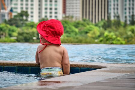 Little girl in the pool on the roof of the hotel. View of the city of Manila from the pool of the luxury five-star Discovery Primea hotel. Sunny weather. Skyscrapers on the background.