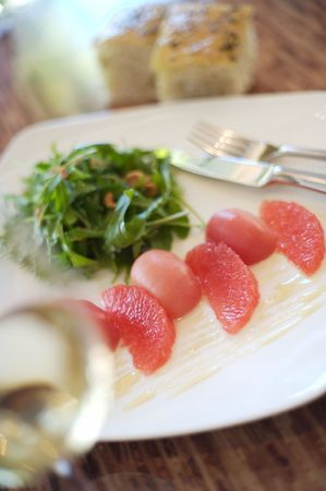 Grapefruit, beet, and rocket salad on a white plate