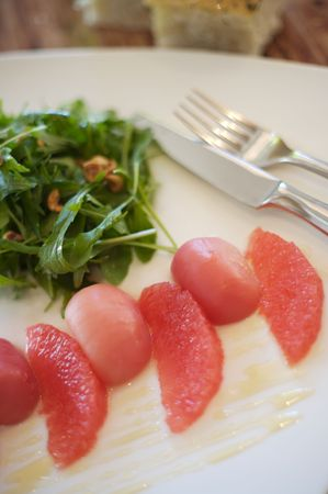 Grapefruit, beet, and rocket salad on a white plate Stock Photo - 2278944