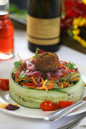 Chopped salad wrapped in cucumber with red wine dressing