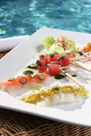 instruct: Sushi and skewered fish served poolside Stock Photo