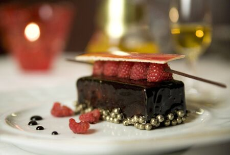Dark chocolate tart with raspberry wafer and gold chocolate caviar pearls