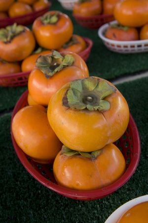 Bright orange persimmons in baskets  Imagens
