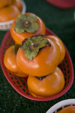Bright orange persimmons in baskets  Stock Photo
