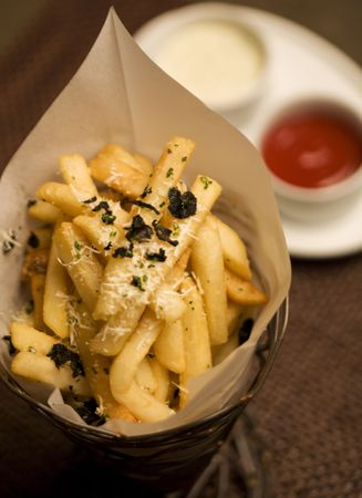 A cone of crispy french fries and house mad condiments
