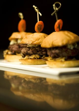 A trio of Kobe Beef sliders served on a flat plate Фото со стока