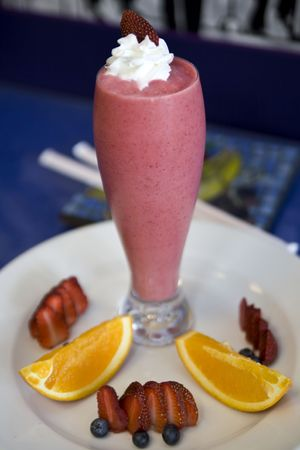 Fresh fruit smoothies topped with whipped cream and blueberries