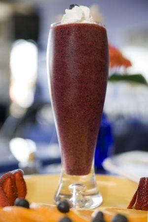 licuados de frutas: Batidos de fruta fresca cubierto con nata montada y ar�ndanos Foto de archivo