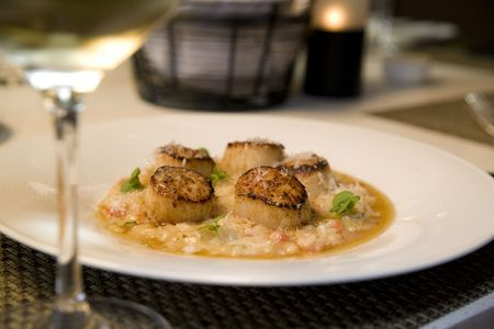 Seared sea scallops on a bed of risotto photo