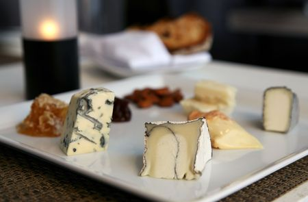 A sampler plate of fine cheeses, chutneys, and smoked nuts.