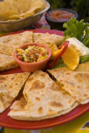 A favorite Mexican snack dressed up with chicken and mango salsa. Stock Photo