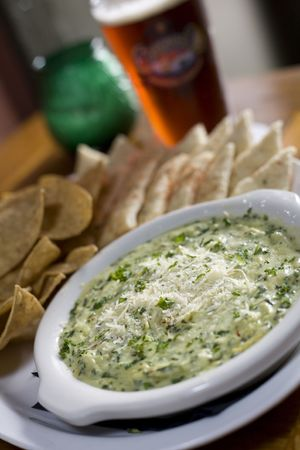 Tangy artichoke dip served with chips and pita wedges from