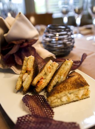 Grilled lobster and cheese sandwich served with purple potato chips. Stock Photo