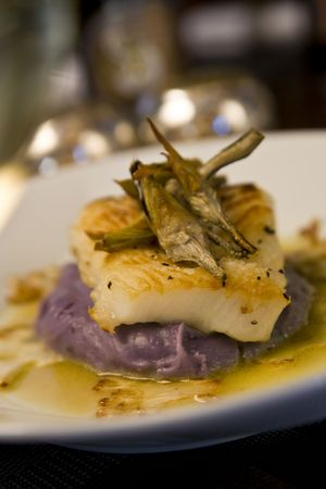 Baked sea bass on a bed of purple potato puree topped with roasted artichoke quarters and cauliflower carpaccio