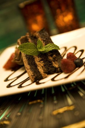 Triple-layered chocolate cake with fresh mint, berries and chocolate sauce