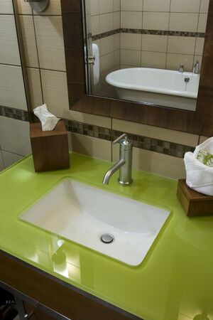 Custom bathroom with green glass counter tops and soaking tub Stock Photo