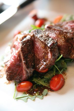 Grilled New York Strip steak on a bed of arugula (rocket) with sliced pear tomatoes. Stock Photo