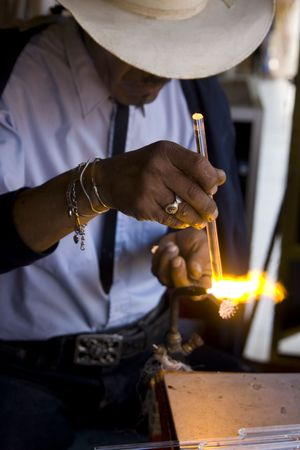 Glass blower working in an open air market in Baja California, Mexico.