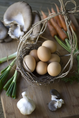 Fresh organic vegetables, eggs, and citrus on a chopping block photo