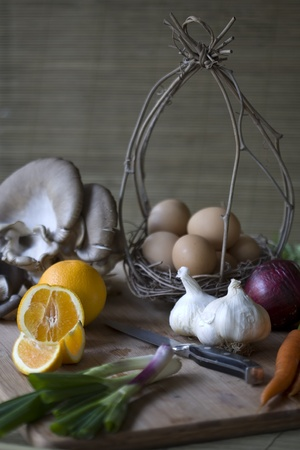 Fresh organic vegetables, eggs, and citrus on a chopping block Stock Photo - 8503912
