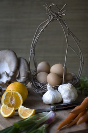 Fresh organic vegetables, eggs, and citrus on a chopping block Stock Photo - 8503913