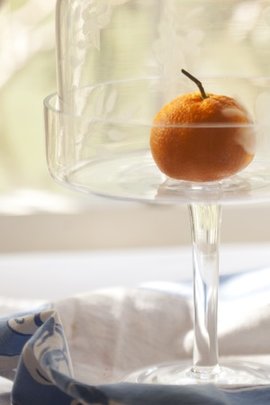 Vintage cut glass cake dish with a tangerine Stock Photo - 12421230