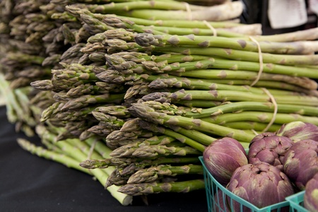Freshly harvested organic asparagus spears with baskets purple artichokes