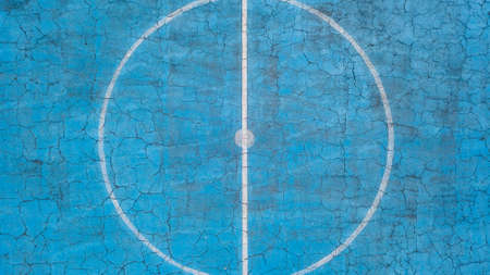 Multi-sport court with central circle and floor painted blue and weathered Banque d'images