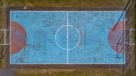 Multi-sport court with central circle and floor painted blue and weathered