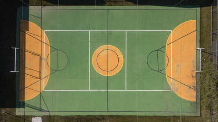 Multi-sport court (volleyball, futsal and basketball), in green and yellow, covered with net and a little dirty due to the weather.