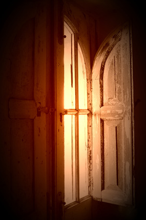 old wood window and sun flare in ancient house photo