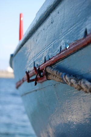 Old blue painted fishing boat tied with rope
