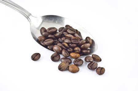A spoon with coffee beans isolated on white background