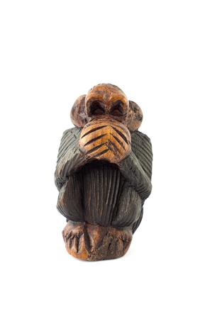 wood sculpture of speak no evil monkey on white background Stock Photo