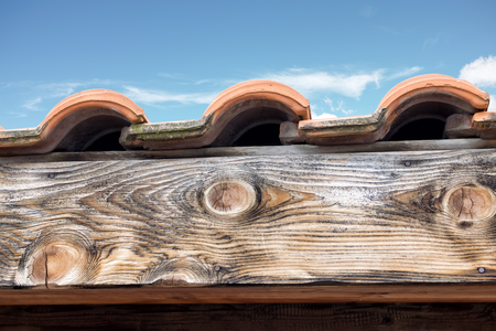 Three roof tiles on wood under blue sky with clouds