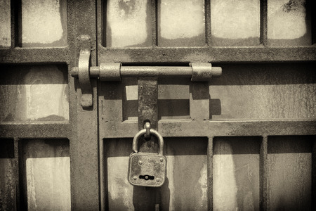 iron latch and padlock  in sepia tone