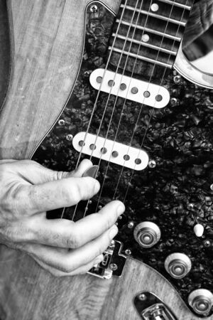 playing electric guitar in black and white