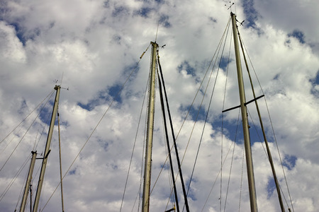 sailboat mast under clouds and blue sky