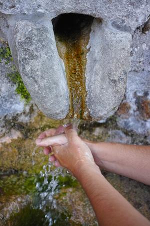 hands washing under stone water source