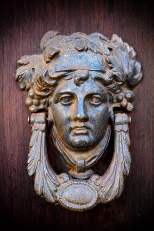 elegant mask knocker on wood door