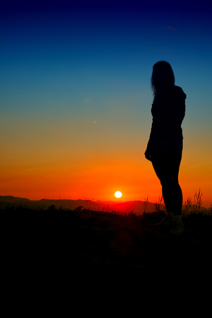 girl silhouette at sunset with blue sky Stock Photo
