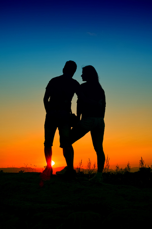 lovers silhouette at sunset with blue sky