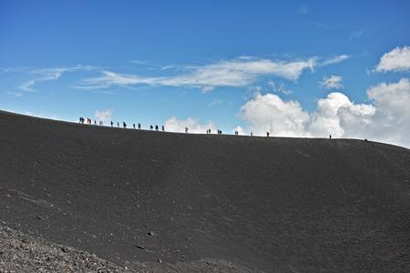People walk on high mountain. Location: Mount Etna