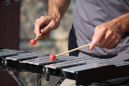 Man playing xylophone with nice red drumstick