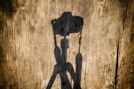Shadow of a camera with a tripod on a wood background
