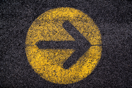 black arrow: arrow sign in yellow circle painted on black asphalt Stock Photo