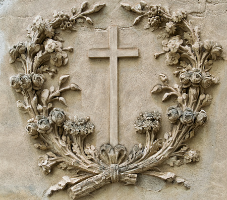 crux: cross in the center of a garland of flowers made on an ancient wall