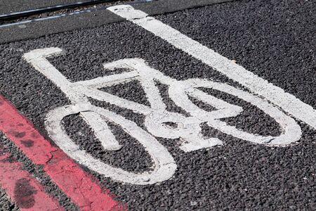 one lane street sign: white asphalt bicycle sign on black asphalt