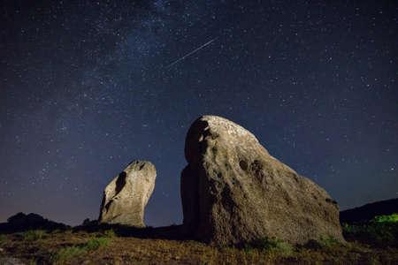 風景: 実際の夜空のペルセウス座流星と 2 つのメンヒル風景します。 写真素材