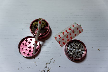 Medical marijuana joint with colored paper,  buds  and grinder lies on a white background. Cannabis, harvest